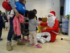 サンタさんが子どもたちにプレゼントを渡している様子
