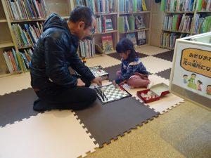 親と子供がチェスで遊んでいる様子